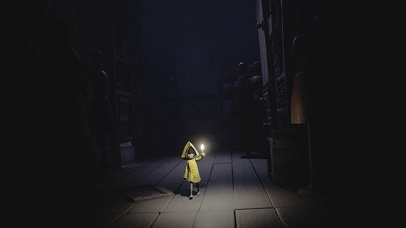 Ein kleines Mädchen im gelben Regenmatel läuft mit einer Kerze in der Hand durch die Dunkelheit. (Spielszene)