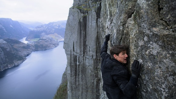 Tom Cruise hängt an einer Felswand (Filmszene)