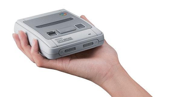Eine Hand hält ein Nintendo SNES Mini.