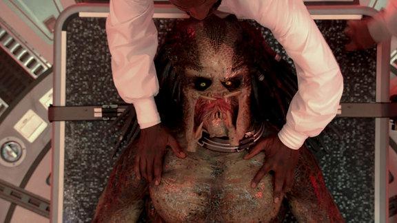 """Der Predator liegt auf einem Behandlungstisch, Filmszene aus """"Predator-Upgrate"""""""