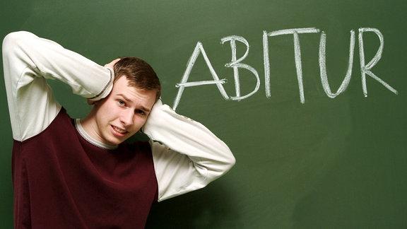 Schüler in Sweatshirt steht für einer Schultafel und umfasst angstvoll seinen Kopf.