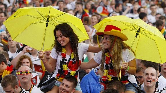 Public Viewing, zwei Mädchen sitzen auf Schultern mit gelben Schirmen in einer Menschenmenge mit deutschen Fußballtrikots