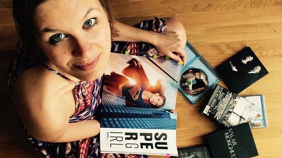 SPUTNIK-Moderatorin Theresa Itzinger sitzt inmitten von DVDs und hält eine Zeitschrift mit Supergirl in der Hand.