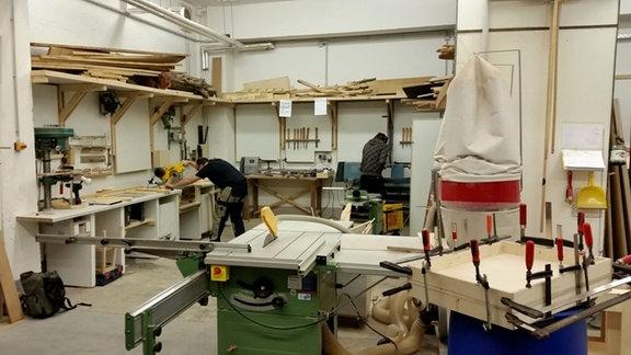 Blick in eine Tischlerwerkstatt mit Kreisäge im Vordergrund.