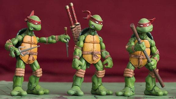 Drei Ninja Turtles stehen nebeneinander. Der Linke ist mit Messern, der Mittlere mit zwei Samurai-Schwertern und der rechts stehende mit einem Kampfstock bewaffnet. Alle drei tragen die typische, rote Augenmaske und Panzerung an Knien, Ellenbogen, Rücken und Brust.