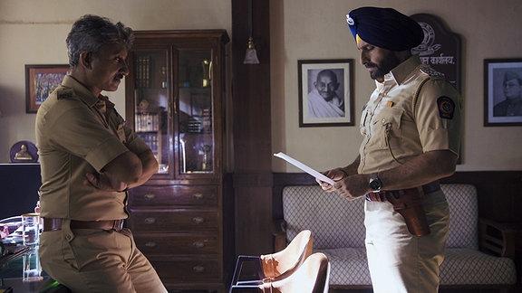 Zwei indische Polizisten stehen sich gegenüber. Einer hält einen Zettel in der Hand und schaut betreten.