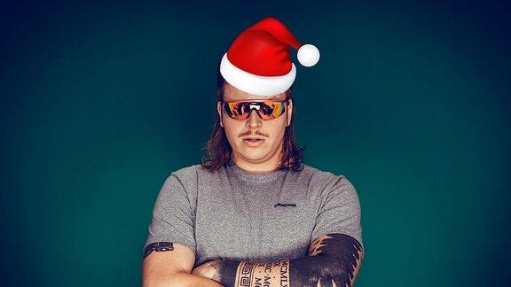 Finch mit verschränkten Armen, Weihnachtsmütze und verspiegelter Brille.