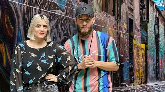 Josi und Greg vor einer Graffiti-Kulisse.