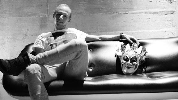 Boris Brechja sitzt auf einer Couch, nehmen ihm liegt eine klassische Karnevalsmaske