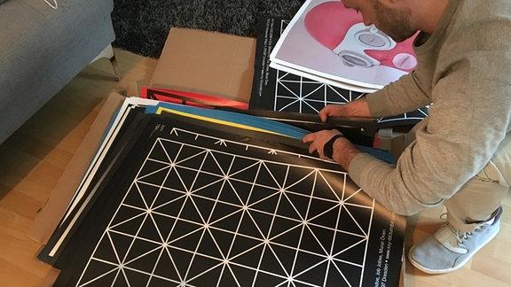 DJ, Labelmacher & Veranstalter Albrecht Wassersleben zeigt Plakate seiner eigenen Partyreihe
