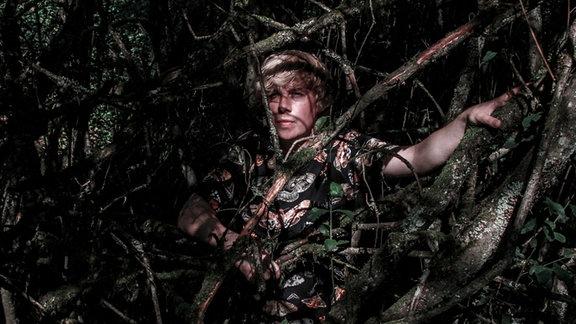 Der DJ Dominik Eulberg späht durch das Unterholz eines Waldes.