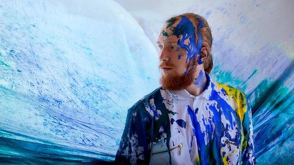 Musiker Niklas Paschburg mit Farbe bespritzt, stehend vor einer Leinwand aus Farbspritzern.