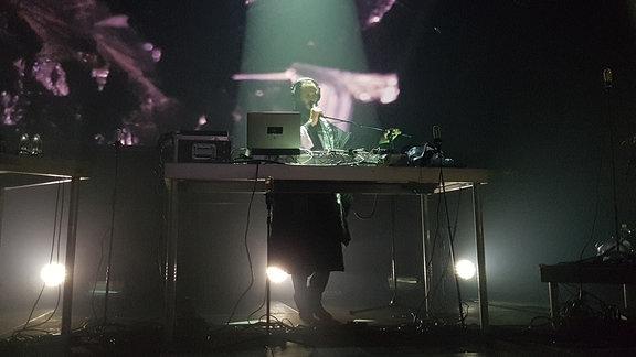 Der Künstler bei einem Auftritt hinter einem DJ Pult.