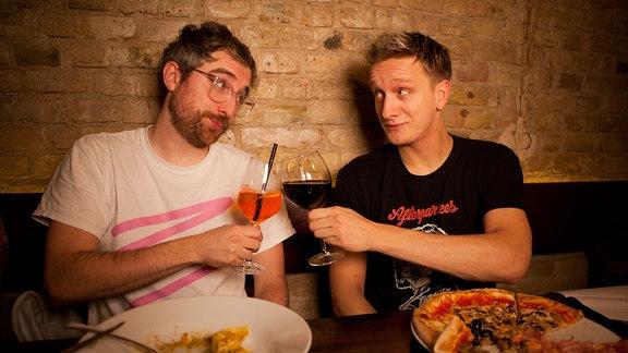 Zwei junge Männer sitzen in einem Restaurant und prosten sich zu.