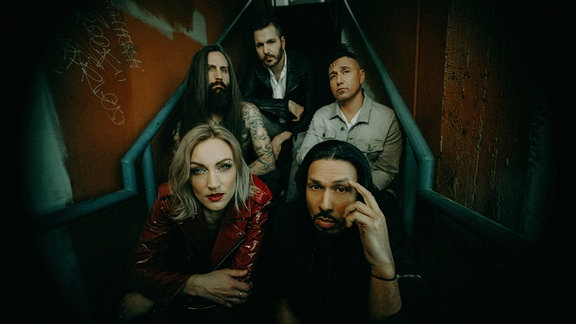 Die fünf Mitglieder der Band Pop Evil sitzen auf einer Treppe.