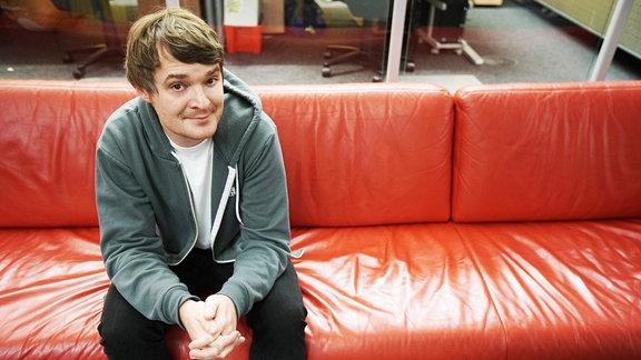 Sebastian Madsen sitzt auf dem roten SPUTNIK-Sofa