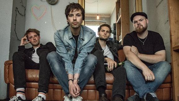 Die vier Bandmitglieder gedrängt auf einem Sofa.