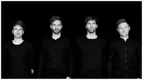Die fünf männlichen Bandmitglieder vor einem schwarzen Hintergrund.