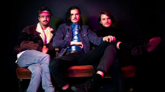 """Die drei Künstler der Band """"Das Moped"""" lümmelt auf einem Sofa."""