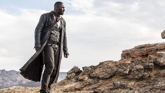 Ein Mann mit einem Ledermantel in einer Wüste