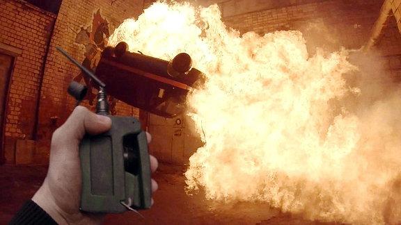Blick aus der Ich-Perspektive: Die linke Hand hält einen Zünder für eine Bombe. Im Hintergrund explodiert ein Auto. Es fliegt durch die Luft und eine große Flamme ist zu sehen. Die Person befindet sich in einer Lagerhalle.