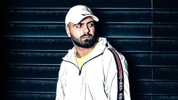 Deutscher Rapper vor einer Wand