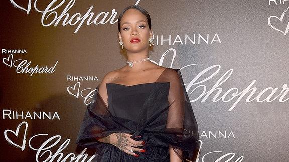 Rihanna steht in einem schicken Kleid vor einer Pressewand.