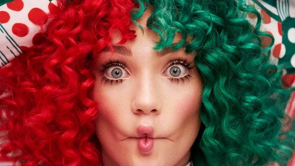 Sia mit rot-grüner Lockenperücke und riesiger Weihnachtsschleife auf dem Kopf. Sia macht einen Fisch-Kuss-Mund.