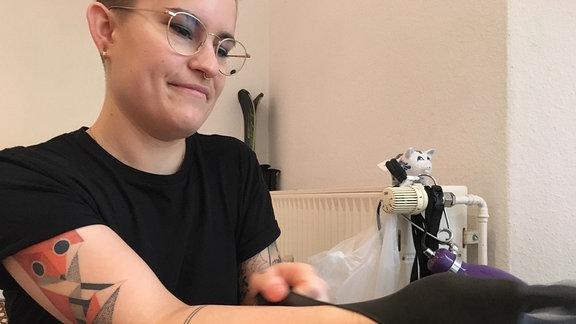 Die Tätowiererin zieht sich die Gummihandschuhe an.