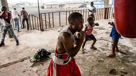 Ein schwarzer Junge trainiert Boxen an einem Sandsack.