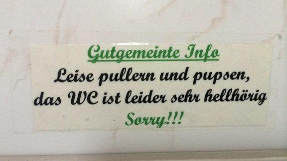"""Ein Zettel mit der Aufschrift """"Gutgemeinte Info: Leise pullern und pupsen, das WC ist leider sehr hellhörig. Sorry!!!"""""""