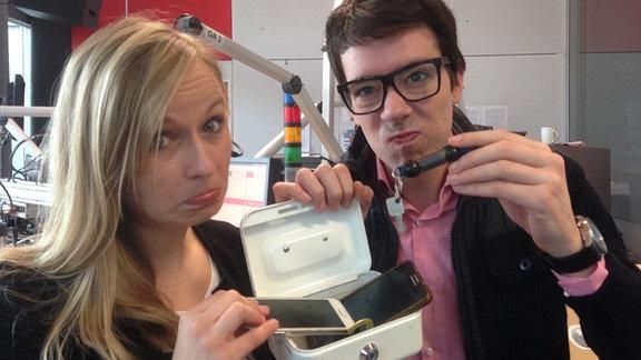 Kathrin und Raimund schließen ihre Handys in eine kleine weiße Geldkassette ein und schauen sehr besorgt drein.