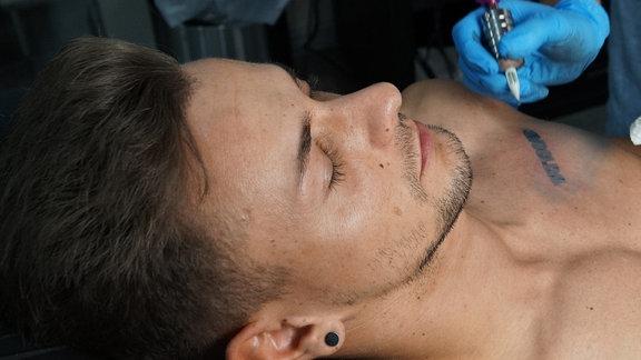Tino lässt sich ein Werbetattoo auf die Brust stechen