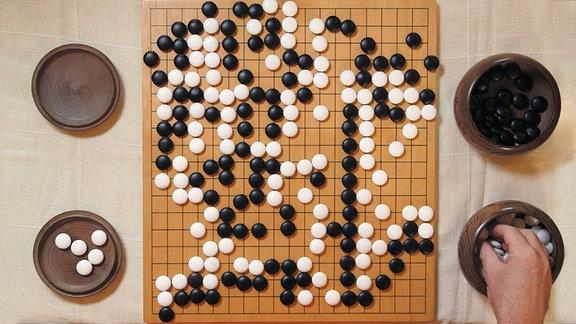 Spielbrett für das Spiel Go mit 19 mal 19 Knotenpunkten und weißen und schwarzen Spielsteinen
