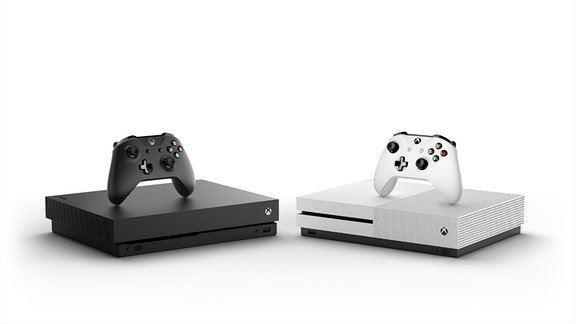 """Zwei Spielekonsolen """"Xbox One X"""" von Microsoft stehen nebeneinander, links schwarz, rechts weiß."""