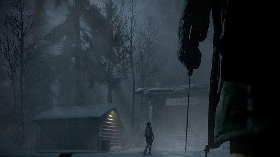 """Eine Hütte im Wald und eine großes Holztor mit der Aufschrift """"The Blackwood Pines"""". Eine junge Frau geht auf das Tor zu. Im Vordergrund sieht man eine Hand, die ein Messer hält."""