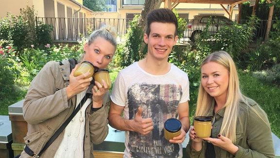Von links im Bild: Vanessa, Yves und Caro mit dem gerade geernteten Honig in Gläsern vor den Bienenkästen.