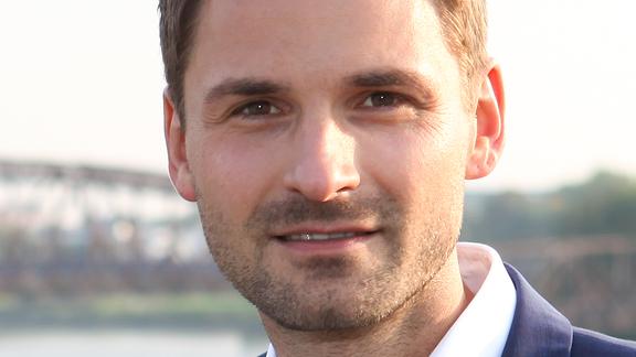 Ein junger Mann mit Dreitagebart und im Anzug blickt freundlich in die Kamera.