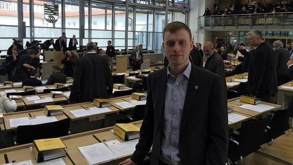 Ein junger Mann im Anzug im Landtag von Sachsen-Anhalt.