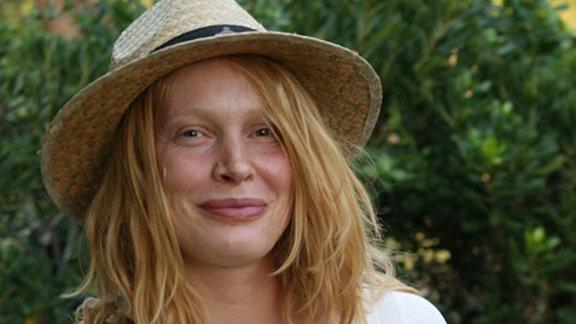 Eine junge Frau steht mit weißer Bluse und Strohhut in einem Park und lächelt in die Kamera.