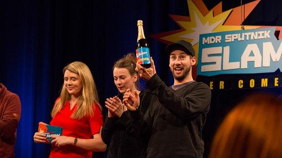 """Beim SPUTNIK Slamedy hält Tobias Kunze eine Sektflasche mit der Aufschrift """"Slamedy Winner"""" hoch."""