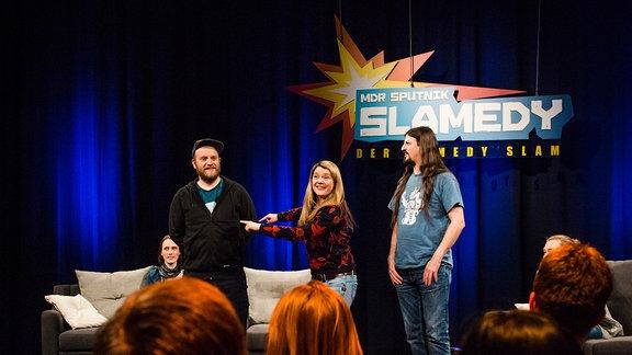 Auf der SPUTNIK Slamedy-Bühne stehen die beides Tagesgewinner Paul Weigl (l.) und Micha-El Goehre. In der Mitte steht Moderatorin Franziska Wilhelm und zeigt auf Paul Weigl.
