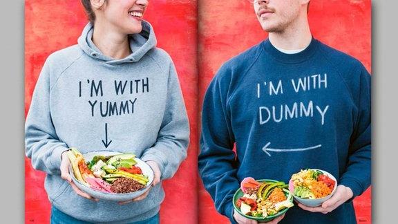 """Deniz Fıçıcıoğlu trägt einen grauen Sweater mit der Aufschrift """"I'm with yummy"""". Sie hält eine Teller voller lecker angerichtetem Gemüse. Felix Bork steht neben ihr. Er trägt einen dunkelblauen Sweater mit der Aufschrift """"I'm with dummy"""". Er hält zwei kleine Schüsseln mit Gemüse in den Händen."""