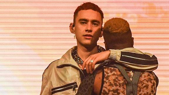 Olly Alexander, Frontmann von Years & Years steht in einem goldenen Anzug auf der Bühne und umarmt einen seiner Tänzer.